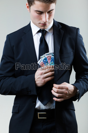 young man in formalwear putting money