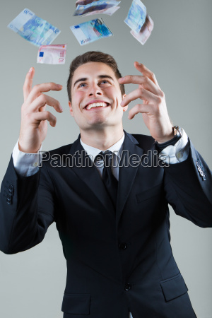 young man in formalwear throwing money