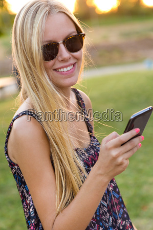 young beautiful girl texting with her