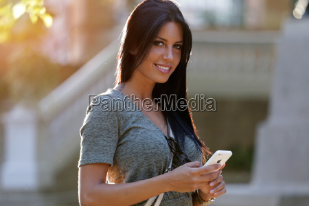 smiling beautiful woman texting with her