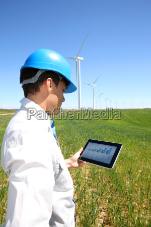 businessman checking on wind turbine energy