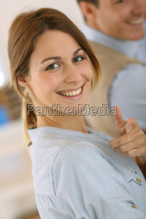 cheerful girl in office showing thumbs
