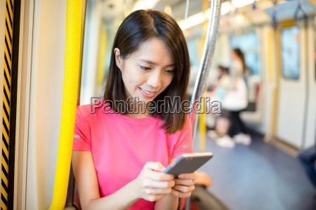 woman use smart phone inside train
