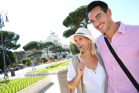 smiling couple of tourists visiting rome