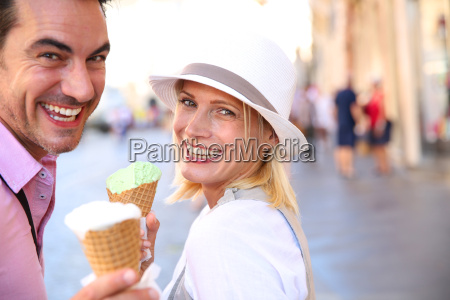 cheerful couple in rome eating ice