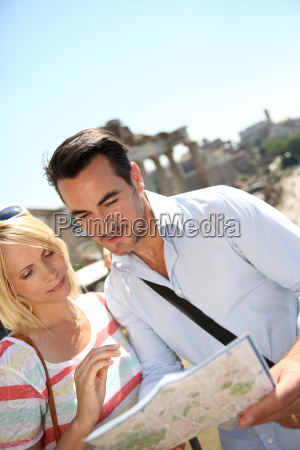 couple of tourists reading city map