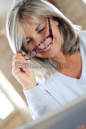 senior woman with eyeglasses websurfing on