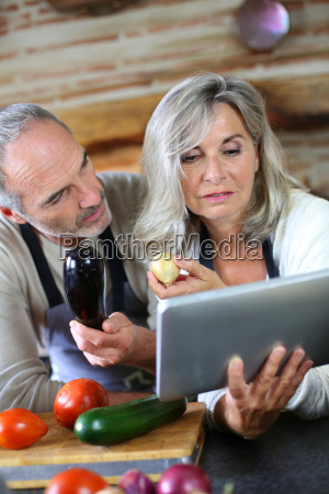 senior couple in home kitchen looking