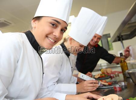 team of young chefs preparing delicatessen