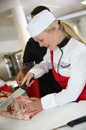 girl cutting meat during butcher training