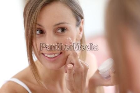 attractive girl putting anti aging cream