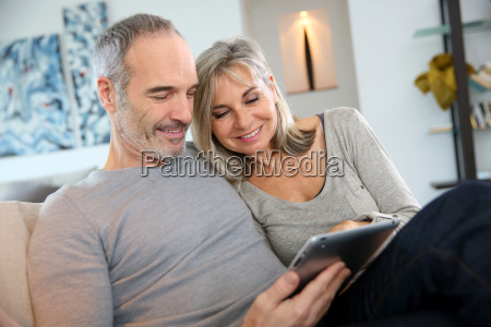 mature couple at home websurfing with