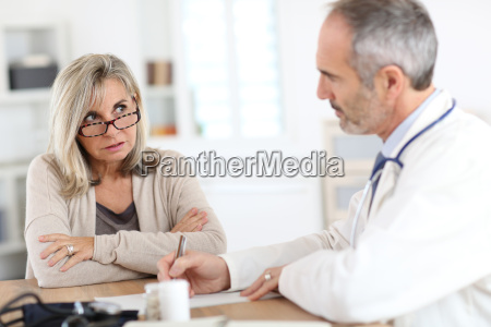 doctor giving medicine to senior woman