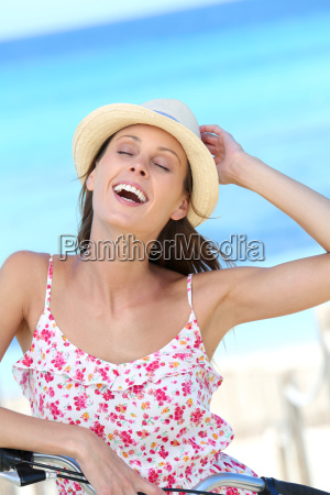 attractive young woman riding bicycle by