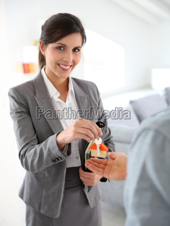 smiling real estate agent giving home