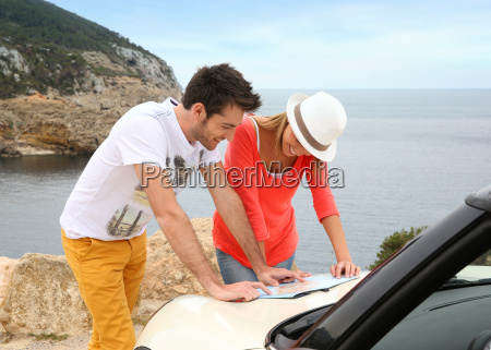 couple reading map on road trip