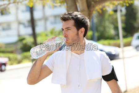 athletic man drinking water after exercising
