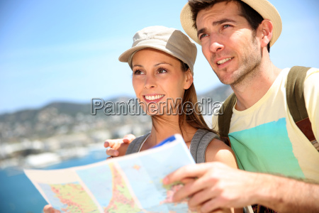 cheerful young couple of travelers reading