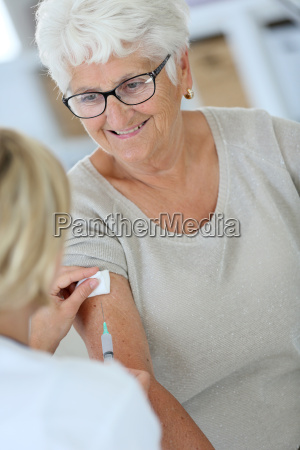 nurse making vaccine injection to elderly