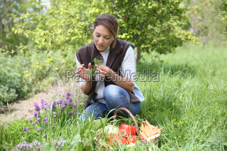 woman in vegetable garden smelling aromatic