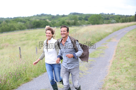 cheerful couple of farmers running in