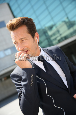 businessman talking on phone outside building