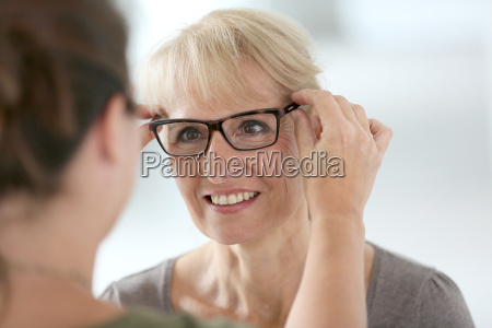 senior woman trying new eyeglasses in