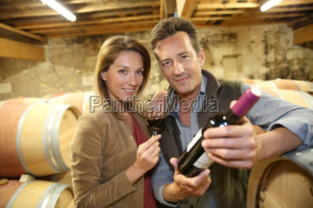 cheerful couple of winegrowers in wine