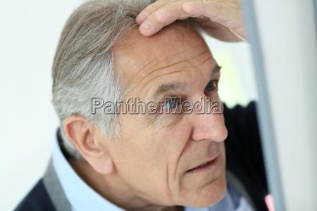 senior man looking at hair loss