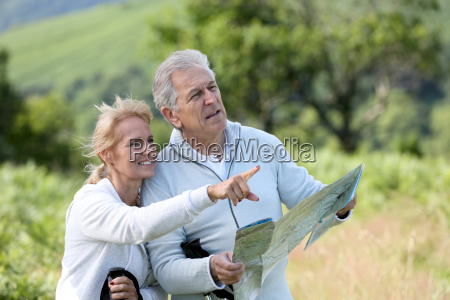 senior hikers reading orientation map