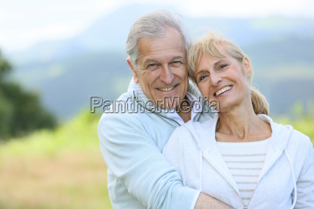 portrait of cheerful senior couple embracing