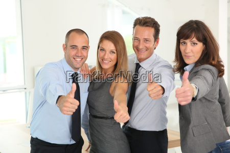 successful business team showing thumbs up