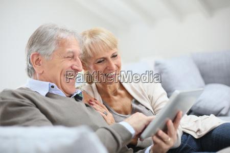 cheerful senior people websurfing on internet