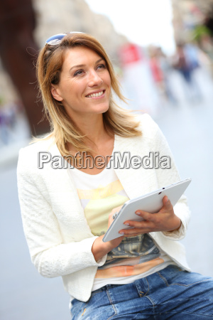 smiling blond woman using tablet in