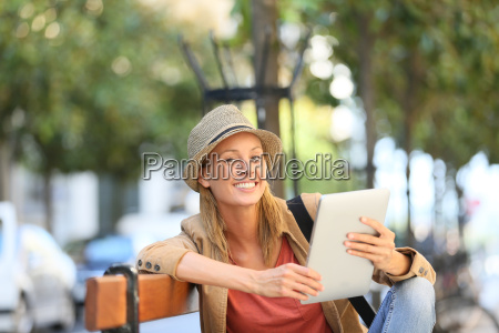 smiling trendy girl using tablet in