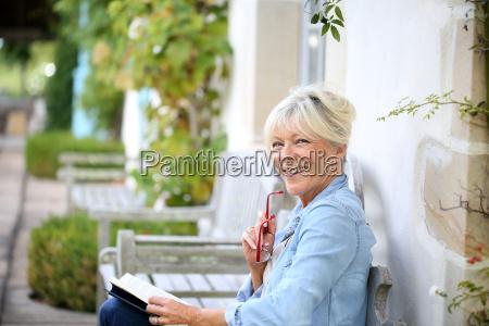 senior woman reading book sit on