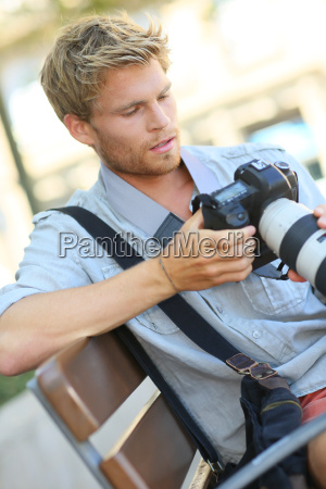 young photographer with camera sitting on
