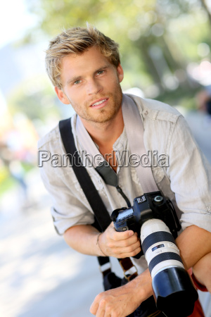 portrait of handsome photographer holding camera