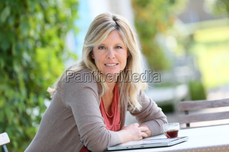mature woman relaxing with tablet and