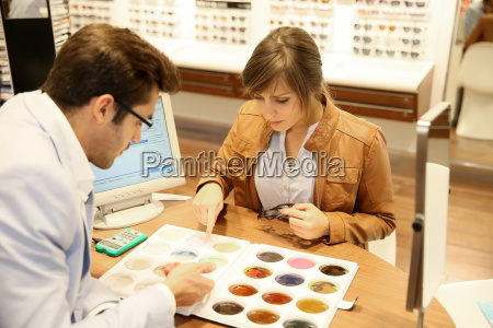 woman with optician choosing spectacle lenses