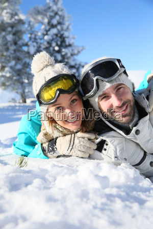 cheerful couple of skiers laying down