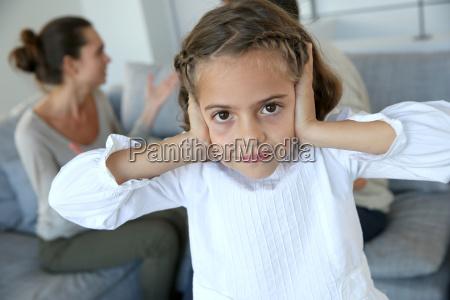 little girl covering her ears not