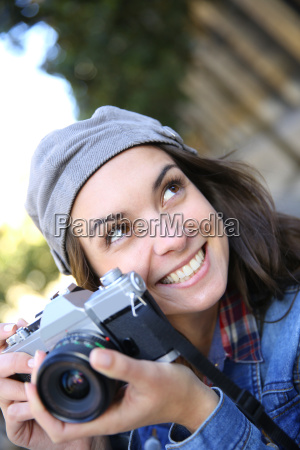 portrait of trendy girl holding camera