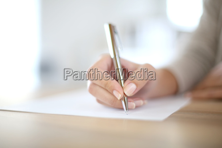 closeup of womans hand writing on