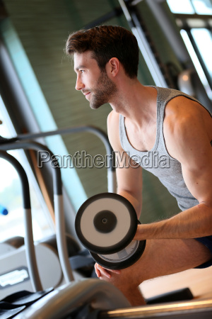 man lifting weights in fitness center