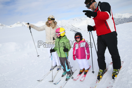 family of four skiing together in