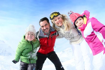 cheerful family of 4 enjoying winter