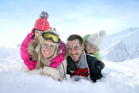 cheerful family laid down in snow