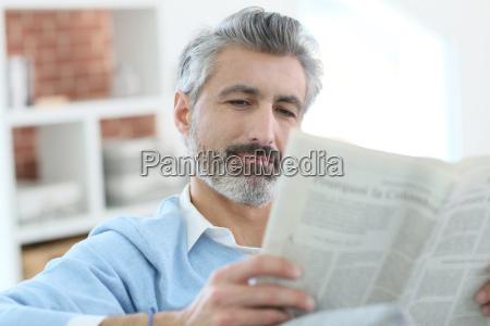 mature man reading newspaper sitting in