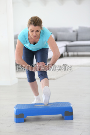 middle aged woman doing stretching exercises